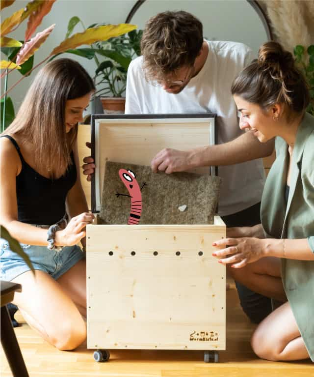 Drei sommerlich gekleidete Personen hocken auf dem Holzboden im Wohnzimmer und schauen in eine Wurmkiste. Außen zwei weiblich gelesene Personen, in der Mitte eine männlich gelesene Person, die den Deckel öffnet und sich darüber beugt. In der Hand hält die Person die Hanfmatte fest. Ein illustrierter Kompostwurm lacht aus der Wurmkiste heraus. Die Personen blicken neugierig und freuen sich über die Entdeckung.