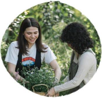 Zwei weiblich gelesene Personen befinden sich in einem Garten. Der Hintergrund ist dominiert von grünen Blättern, die Personen halten gemeinsam einen geflochtenen Korb fest, in den sie einen Blumenstock einsetzen. Die linke Person wendet das Gesicht der Kamera zu, lächelt in Richtung der Blumen. Sie trägt ein weißes T-Shirt mit rotem Print und darüber eine schwarze Latzhose und hat schulterlange braune Haare. Die rechte Person ist im Profil zu sehen und wendet ihr Gesicht dem Korb zu. Die lockigen schwarzen Haare verdecken das Gesicht. Die Person trägt ein zartgrünes Langarmshirt und darüber eine grüne Latzhose.