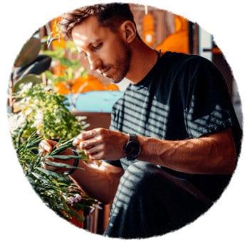 Männlich gelesene Person mit kurzen braunen Haaren und schwarzem T-Shirt hält die Blätter einer Zimmerpflanze in der Hand und begutachtet sie eingehend. Sonnenlicht scheint durch die Jalousienschlitze auf die Person. Warmes Licht, angenehme Stimmung. Die Person ist konzentriert.